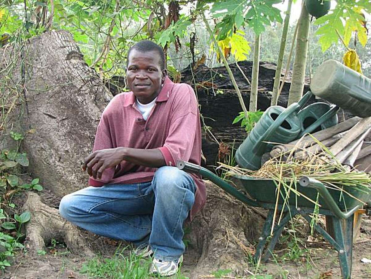 Arthur Bondo, 25, lost his right arm as a child soldier after being shot in a gun battle near Monrovia. He is now trying to learn farming skills.