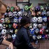 Two pedestrians walks past a display of Lucha libre masks in the MIssion district between 24th and South Van Ness Ave in San Francisco, Calif. on Sunday, Aug. 30, 2009.