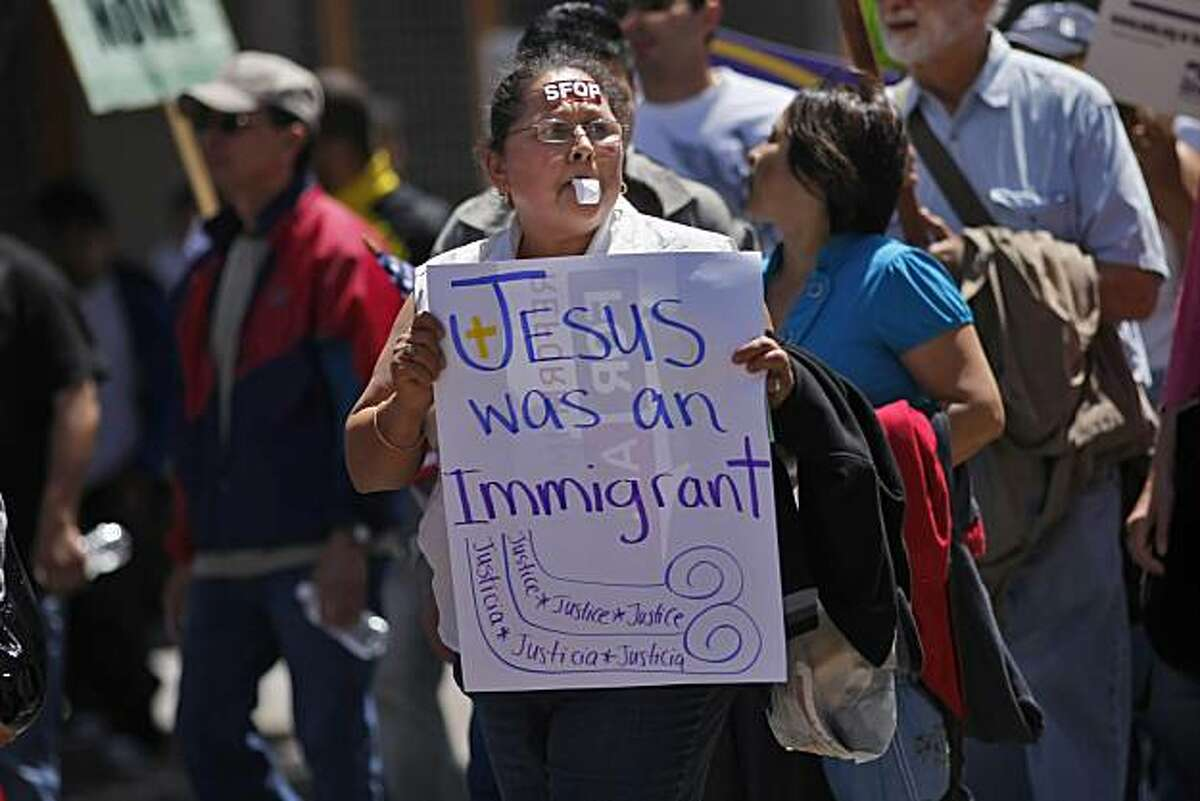 Ana V. Gutierrez carries a sign as she marches through the Mission District to Civic Center with thousands of protesters Saturday in San Francisco.