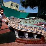 Four year old Angie Rosales plays on the giant mosaic sculpture of Quetzalcoatl at the 24th Street/York mini park.