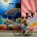 "A bicyclist rolls past murals painted on buildings lining Clarion Alley in the Mission District in San Francisco, Calif., on Thursday, July 30, 2009. The murals are featured in a book titled, ""Street Art San Francisco,"" which highlights the colorful murals of the Mission District."