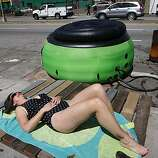 Brooke Cooley works on her suntan while waiting for a hot tub to be hooked up on Cesar Chavez Boulevard near Mission Street in San Francisco on Saturday. Residents upset with a proposed ban on sitting or lying on sidewalks staged events across the city to protest the legislation.