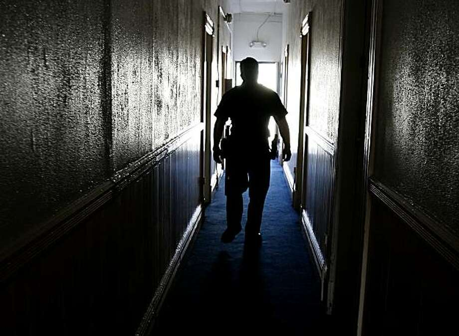 SFPD officer Pete Shields walks down a dark hallway of a small Mission district hotel where neighbors have heard someone screaming for help.  The Mission Police Station on San Francisco's Valencia Street is responsible for 2.7 miles of the city. It serves 84,000 residents in the Mission, Noe Valley and Castro districts, from the arty stores in Noe Valley to the gangs on 24th Street.  {Brant Ward/San Francisco Chronicle}4/24/07 Photo: Brant Ward, The Chronicle