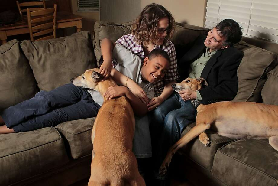 Debbie Clawson and Edward Souza cuddle with Michael, Debbie's son, and two of their Greyhounds, Sunday March 6, 2011, in Brentwood, Calif. THe couple meet when Debbie was fostering Indy and Edward wanted to adopt him. The couple now are expected to marry in October. Photo: Lacy Atkins, The Chronicle