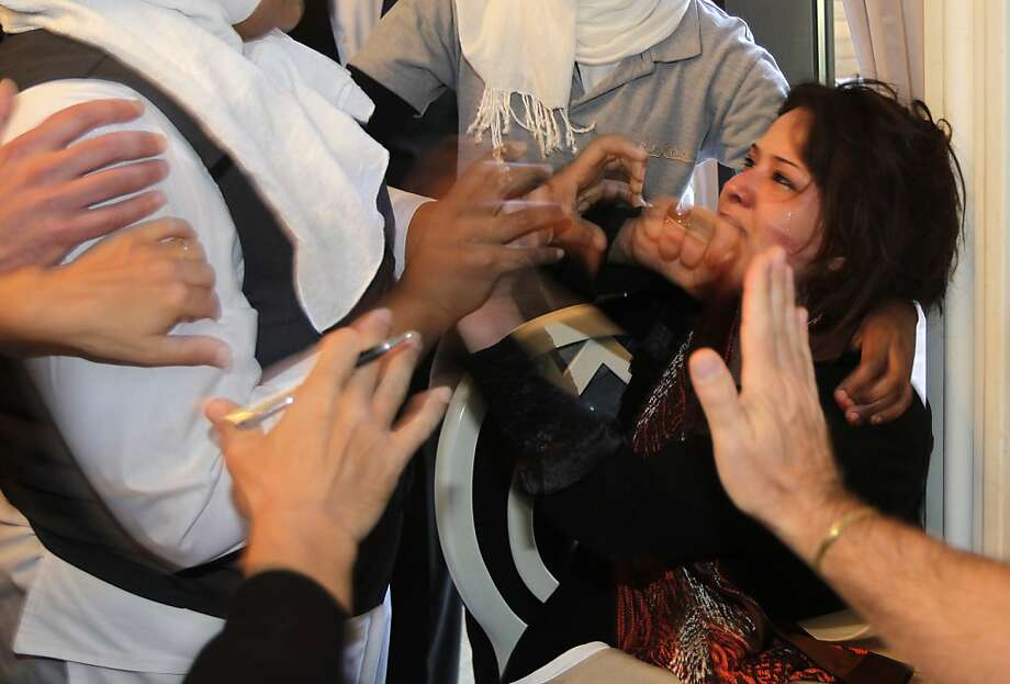 Hands from hotel employees trying to grab her, and foreign journalist attempting to protect her, surround Iman Al-Obeidi, right,  who said she spent two days in detention after being arrested at a checkpoint in Tripoli, Libya, and was sexually assaulted by up to 15 men while in custody  in Tripoli Saturday March 26, 2011, after storming into the hotel's breakfast room to show her wounds to foreign media. A scuffle between hotel employees, information ministry officials and plain clothe police trying to grab her and stop the press for filming on one side and foreign media representatives followed. Two cameras were smashed on the ground and at least one reporter was beaten and kicked.   Al-Obeidi was later taken in a car to an undisclosed location. Photo: Jerome Delay, Associated Press