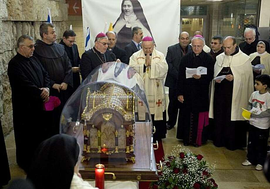 Catholic clergy pray during a ceremony welcoming the relics of St. Therese of Lisieux upon their arrival at Ben Gurion airport near Tel Aviv, Israel, Monday, March 14, 2011. Remains from St. Therese of Lisieux, a revered French nun who died more than 100years ago, have traveled the world, ventured into outer space and been worshipped by hundreds of thousands of Roman Catholics. On Monday the relics arrived to Israel on a flight from Brussels and will be touring the Holy Land. Photo: Ariel Schalit, AP