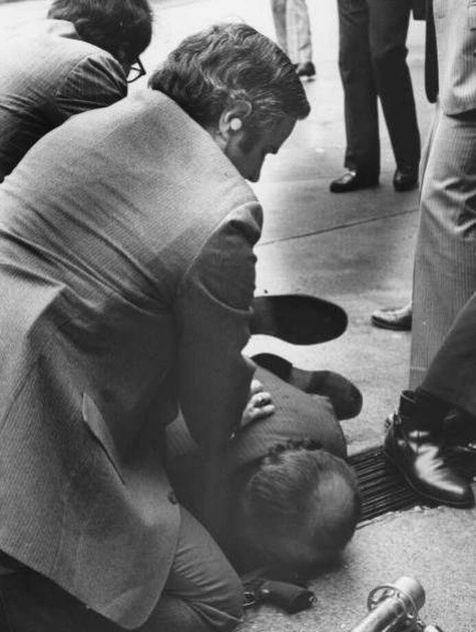 A secret agent tends to Presidential Press Secretary James Brady laying wounded on the ground after John Hinckley in an attempt to assassinate President Ronald Reagan on March 30, 1981 fired six shots with a pistol. (UPI Photo/Don Rypka/Files) Photo: Don Rypka, UPI 1981