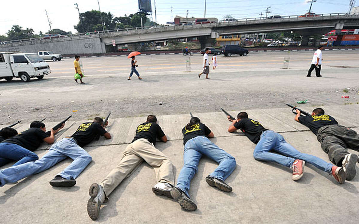 Applicants for private security guards aim their wooden replica rifles during markmanship training in front of a security agency school in Manila on April 8, 2010. The applicants undergo a 15-day training before they are employed as private security guards. According to a government figure released on December 2009, unemployment in the Philippines rose to 7.1 percent in October 2009, up from the 6.8 percent posted for the month in 2008.