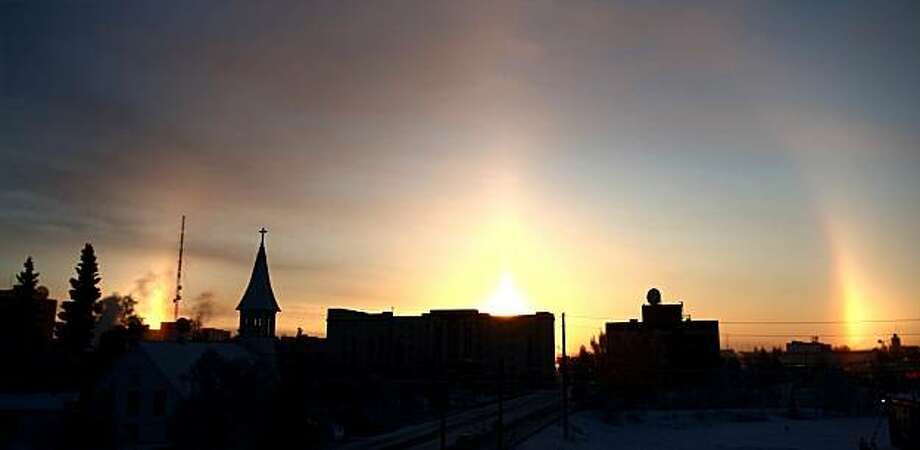 Sundogs: When the sun's rays pass through ice crystals in the atmosphere, mini-suns can appear at its sides, as in this photo from Fairbanks Alaska, Legend has it that the ancient Greeks figured Zeus was out walking his pooches. Actually, Apollo was the sun god, but who wants to ruin a good story? Photo: John Wagner, Fairbanks Daily News-Miner