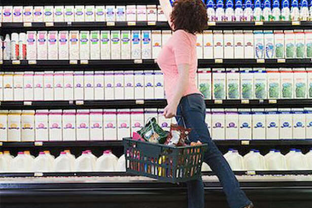 """Not one for the mall? Try these exercises from Carson next time you make a run to the grocery store.    If you're purchasing only a few items, carry a basket as you shop.  After your groceries are bagged, carry them to your car. A gallon of milk weighs approximately 10 pounds!    When reaching for an item on a lower shelf, squat.  Repeat two to three times to work your calves, thighs, glutes, and abs.    Reach for items high on shelves; hold for 10 seconds.  Repeat this five times. If you feel self-conscious, pretend you can't decide whether to buy the product. Stretching on your toes with your arms above your head strengthens the legs, back, and arms. It also improves balance.    Grasp the grocery-cart handle tightly on both sides and try to pull your hands apart.   Hold for 10 seconds and repeat. This strengthens your shoulders and the back of your arms.    Grasp the middle of the cart handle with one hand and push right and left for five turns.   Alternate hands. This will work your shoulders, arms, and abs.    Spread your legs to the width of your shoulders.  Try to squeeze the floor together between your feet, holding for 10 seconds. Then push your feet apart and hold for 10 seconds. These two exercises will firm up your inner and outer thighs.    While your groceries are being checked, stand on one leg, straighten your body, and bend one knee.  Hold for 90 seconds and repeat with the other leg. This will improve your balance and strengthen your ankles.    Looks like Carrie Bradshaw was right when she said, """"Shopping is my cardio."""" So go ahead: Swing by a sale at Bloomingdale's - a girl needs her exercise after all!     Reprinted with Permission of Hearst Communications, Inc. Originally Published:  Shopping Workout: How to Burn Calories at the Mall  Masterfile Masterfile"""