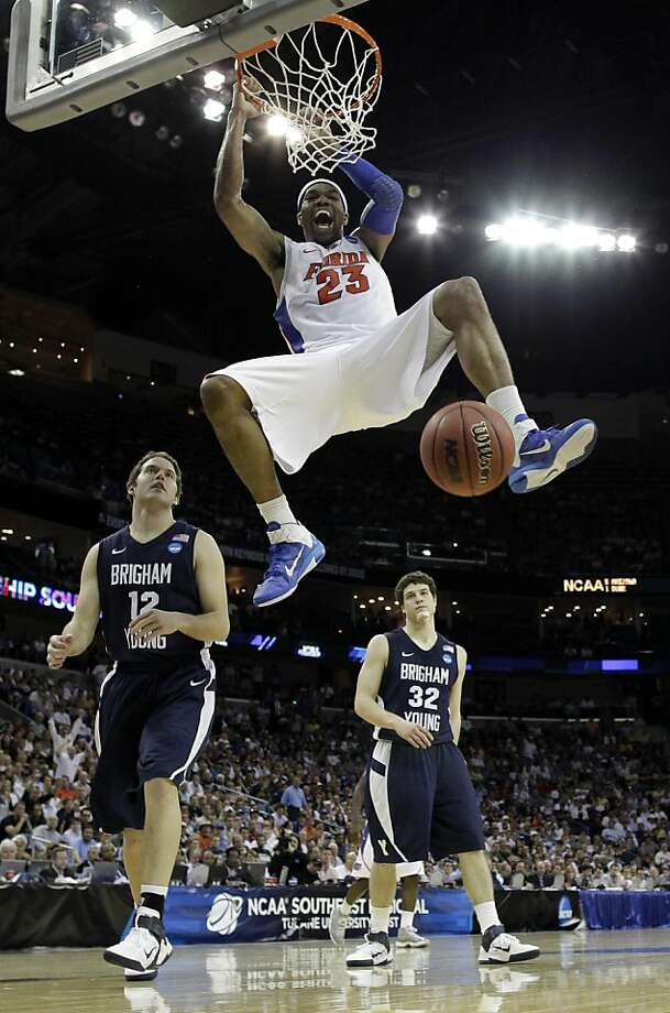 Florida's Alex Tyus (23) dunks in front of BYU's Jimmer Fredette (32) and Logan Magnusson (12) during overtime of the NCAA Southeast regional college basketball semifinal game Thursday, March 24, 2011, in New Orleans. Photo: David J. Phillip, AP