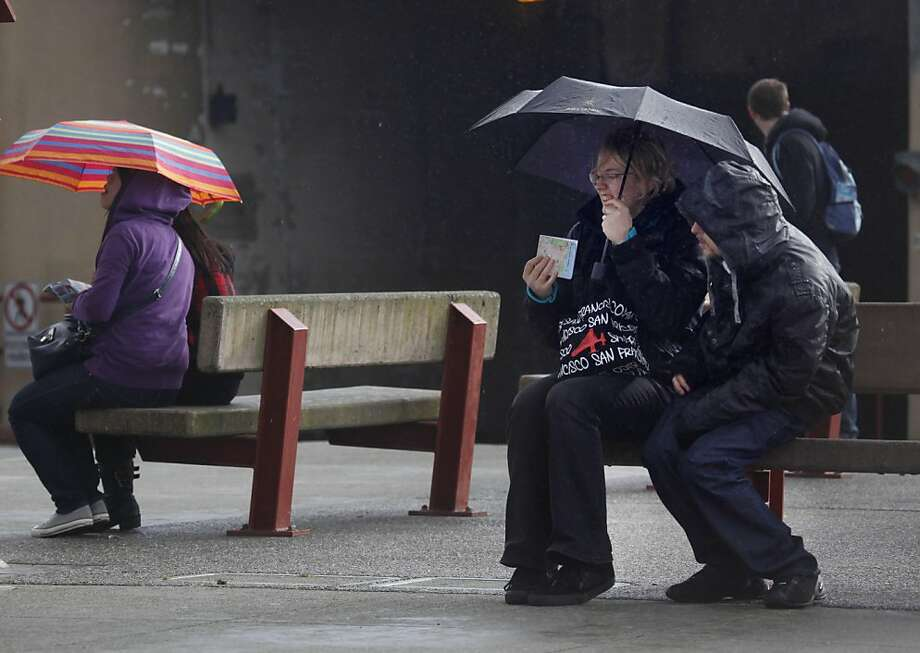Nadja Drewes (second from right) and Jerome Rey (right), both of Switzerland, share an umbrella while they look at a map near the Golden Gate Bridge on Wednesday, March 23, 2011 in San Francisco, Calif. Photo: Lea Suzuki, The Chronicle