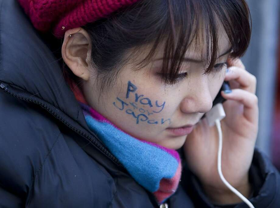 Ayano Tominaga talks on her iPhone with a written message on her face about the Japan tsunami while waiting in line to purchase Apple Inc.'s iPad 2 which goes on sale today at 5 p.m. in New York, U.S., on Friday, March 11, 2011. Apple Inc. may sell 600,000 of the second version of the iPad when it debuts this weekend, extending the device's lead in a crowding market. Photographer: Jin Lee/Bloomberg *** Local Caption *** Ayano Tominaga Photo: Jin LKee, Bloomberg
