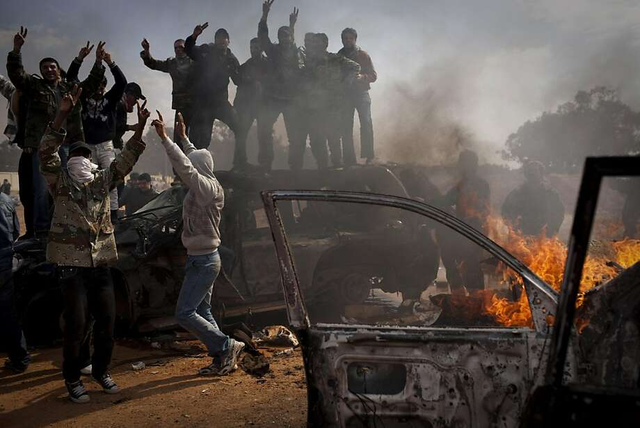 Libyan rebels celebrate next to burning cars after Libyan leader Moammar Gadhafi's forces where pushed back from Benghazi, eastern Libya, Saturday, March 19, 2011. Explosions shook the Libyan city of Benghazi early on Saturday while a fighter jet was heard flying overhead, and residents said the eastern rebel stronghold was under attack from Muammar Gaddafi's forces. Photo: Anja Niedringhaus, AP