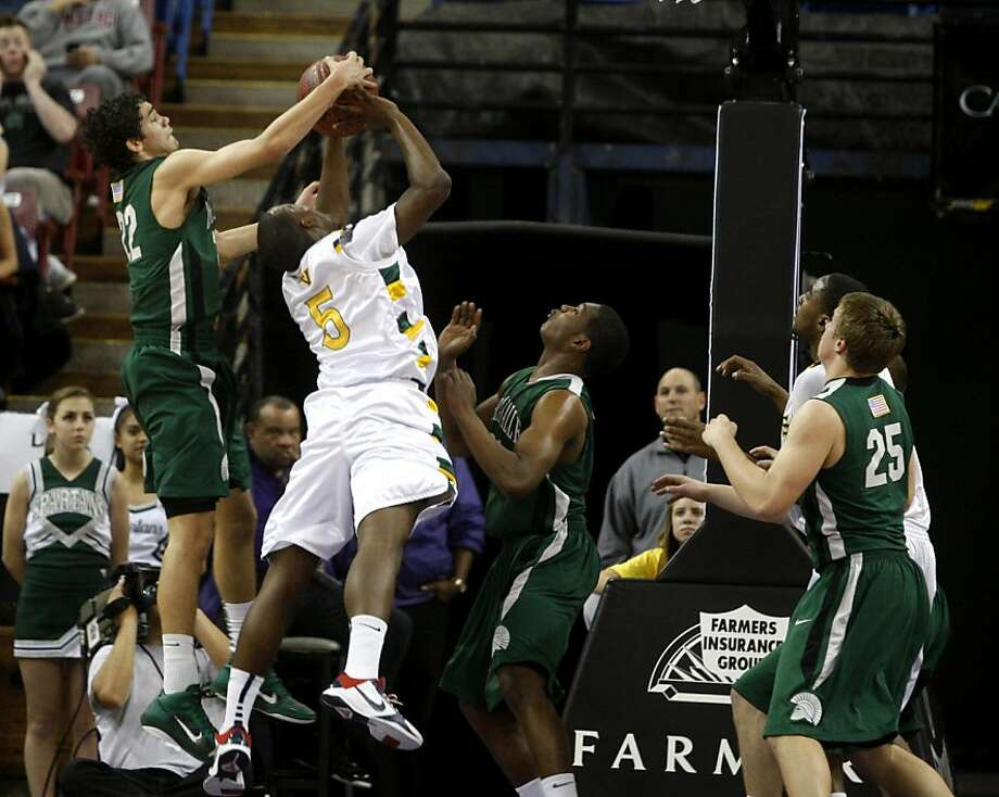 Spartan's Elliot Pitts blocks Trojan's Roderick Bobbitt during the NorCal championship Division I regional finals at the Power Balance Arena in Sacramento, Calif., on Saturday, March 19, 2011. De La Salle Spartans defeated the Castro Valley Trojans 49-43. Photo: Thomas Levinson, The Chronicle