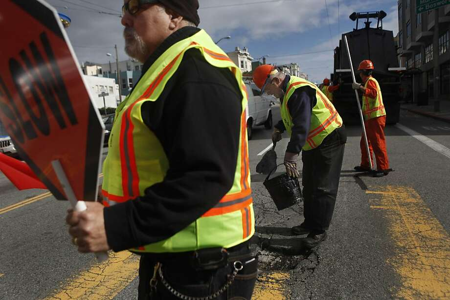Ben Santana (left) Department of Public Works asphalt plant supervisor monitors traffic as  Department of Public Works asphalt workers  Ken Barros (center) and Ricky Limjoco repair a pothole on Mission Street on Tuesday, March 22, 2011 in San Francisco, Calif. Photo: Lea Suzuki, The Chronicle