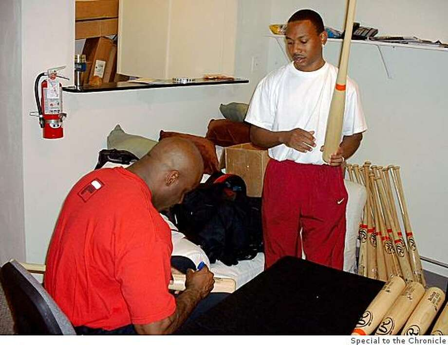 Barry Bonds autographing bats as his then - business manager Steve Hoskins looks on in this undated photo. Photo: Special To The Chronicle