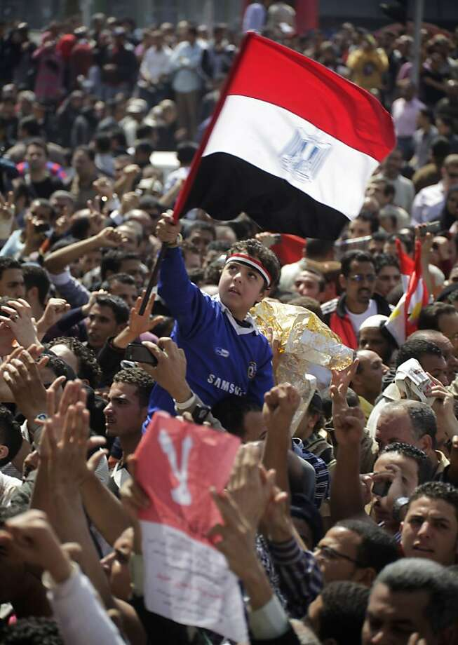 "An Egyptian boy raises Egypt's flag during a protest against the referendum amending the constitution at Tahrir Square in Cairo, Egypt, Friday, March 18, 2011 a day before the referendum . Civic groups have raised fears that the timing of a Saturday's referendum on constitutional amendments and June parliamentary elections followed by a presidential vote are too rushed to permit a true representative democracy to emerge. Arabic read "" NO"". Photo: Amr Nabil, Associated Press"