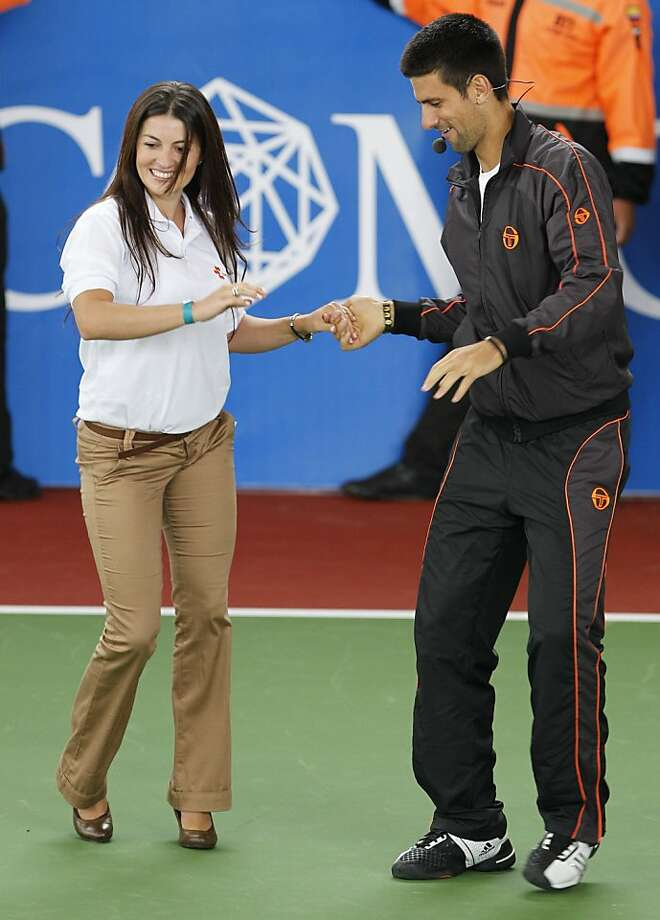 Tennis player Novak Djokovic, of Serbia, right, dances a woman member of the audience before an exhibition match against Rafaen Nadal, of Spain, in Bogota, Colombia, Monday, March 21, 2011. Photo: Fernando Vergara, AP