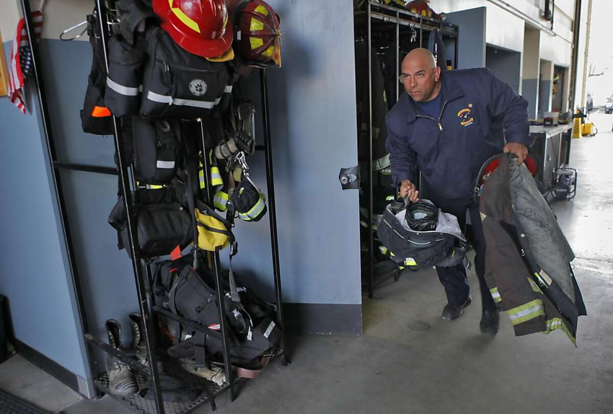 Lieutenant Chuck Garcia, grabs his suit and helmet before getting on the engine leaving from Station 1, Wednesday March 16, 2011, in Oakland, Calif.