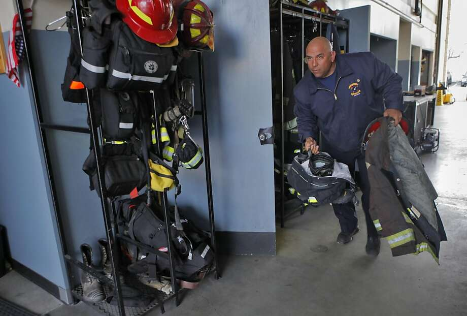 Lieutenant Chuck Garcia, grabs his suit and helmet before getting on the engine leaving from Station 1,  Wednesday March 16, 2011, in Oakland, Calif. Photo: Lacy Atkins, The Chronicle