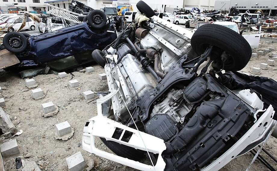 Destroyed vehicles initially gathered for export remain flipped at Sendai Port, Sendai, Miyagi Prefecture, northeastern Japan, Thursday, March 24, 2011. The cars, which were waiting to be exported, were washed away from their parking area by the March 11tsunami. Photo: Shizuo Kambayashi, AP