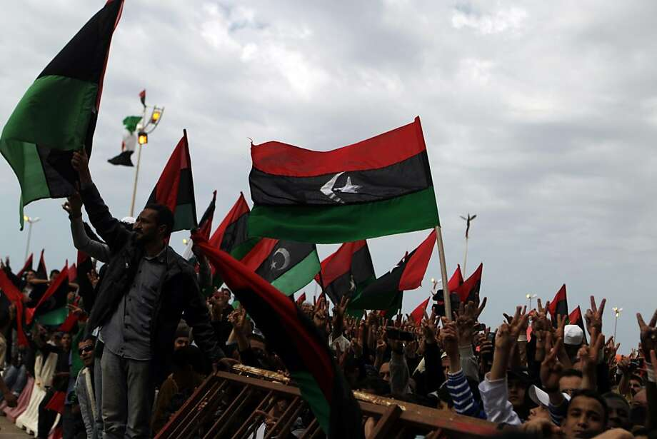 Libyan anti-government protesters wave the flag of the former Libyan monarchy as they gather to celebrate in the eastern rebel-held city of Benghazi city on March 18, 2011 after a UN vote, led by France and Britain, approved a no-fly zone. Photo: Patrick Baz, AFP/Getty Images