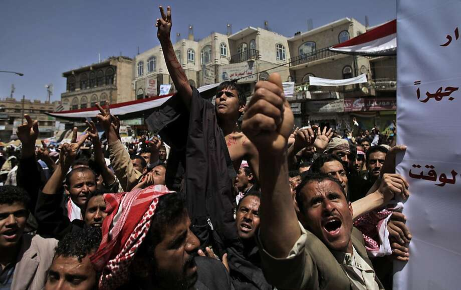 "Anti-government protestors shout slogans during a demonstration demanding the resignation of Yemeni President Ali Abdullah Saleh, in Sanaa,Yemen, Monday, March 21, 2011. Three Yemeni army commanders, including a top general, defected Monday to the opposition calling for an end to President Ali Abdullah Saleh's rule, as army tanks and armored vehicles deployed in support of thousands protesting in the capital. With the defection, it appeared Saleh's support was eroding from every power base in the nation _his own tribe called on him to step down, he fired his entire Cabinet ahead of what one government official said was a planned mass resignation, and his ambassador to the U.N. and human rights minister quit. Banner at right in Arabic reads, "" Loudly, t Photo: Muhammed Muheisen, AP"
