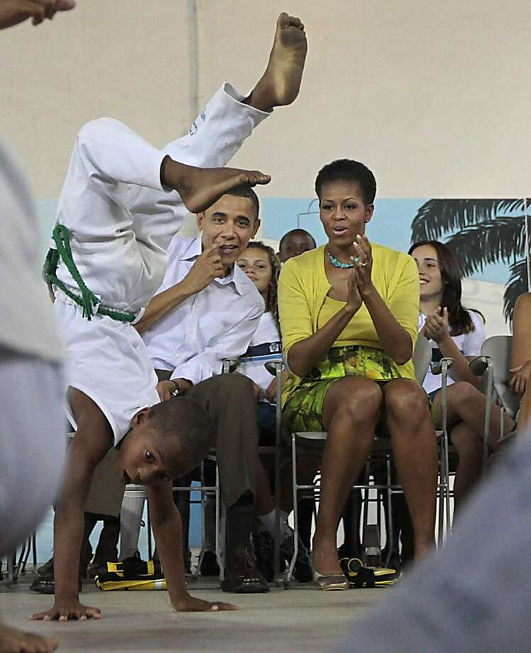 U.S. President Barack Obama, left, with first lady Michelle Obama, right, watch a capoeira performance during their tour of the Ciudad de Deus Favela in Rio de Janeiro, Brazil, Sunday, March 20, 2011. Photo: Pablo Martinez Monsivais, AP