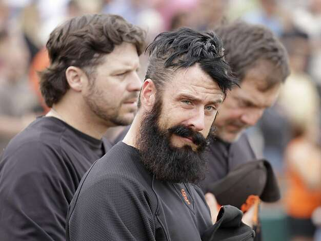 San Francisco Giants relief pitcher Brian Wilson, center, stands between spring instructor Ryan Klesko, left, and manager Bruce Bochy, right, while listening to the national anthem before their spring training baseball game against the Oakland Athletics in Scottsdale, Ariz., Sunday, March 20, 2011. Wilson was recently injured with a strained rib cage muscle and is uncertain for opening day. Photo: Eric Risberg, AP