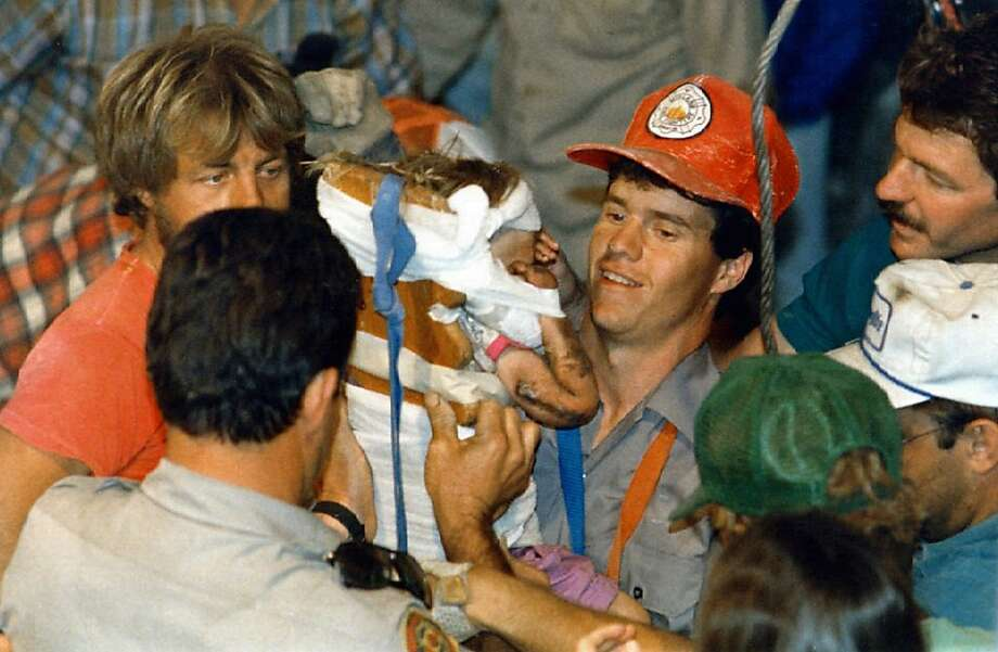 FILE - In this October 1987 file photo, rescue workers carry 18-month-old Jessica McClure to safety in Midland, Texas after she was trapped for 58 hours after she plunged 22 feet into an abandoned water well. Now married with two children, Jessica McClureMorales turns 25 on March 26 and gains access to a trust fund of up to $800,000, the result of donations from thousands of sympathetic strangers across the globe glued to the television for the 58 hours until she was freed. Photo: Eric Gay, Associated Press