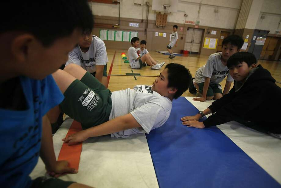 Seventh grader Jason Wu (center) demonstrates sit ups while other Francisco Middle School students monitor his position on Thursday, March 23, 2011 in San Francisco, Calif. Photo: Lea Suzuki, The Chronicle