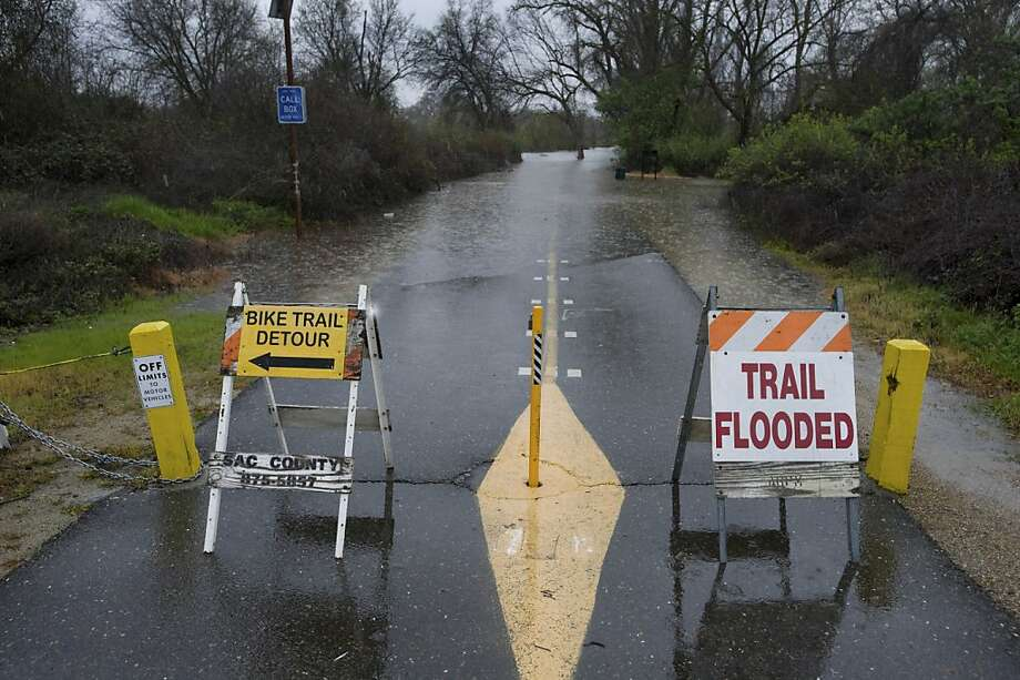 The flooded road is closed at the American River Bike trail at Northgate and Del Paso Blvd. in Sacramento, Calif., Friday, March 18, 2011. The National Weather Service issued a flood watch for much of the Central Valley through Sunday and a winter storm warning through early Saturday for the Sierra Nevada, where as much as 3 feet of snow is predicted by Saturday. (AP Photo/The Sacramento Bee, Manny Crisostomo)  MAGS OUT; TV OUT; MANDATORY CREDIT Photo: Manny Crisostomo, AP