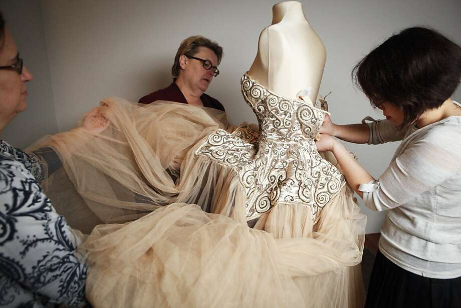 Beth Szuhay, left, textiles conservator for the Fine Arts Museums of SF, Chris Paulocik, conservator at the Metropolitan Museum of Art in New York City, and Joyce Fung, research associate at the Costume Institute at the Metropolitan Museum of Art dress a mannequin with a Cristobal Balenciaga pale pink ballgown with embroidered bodice and tulle skirt, autumn/winter 1950-1951 on Friday, March 11, 2011 at the de Young Museum in San Francisco, Calif.    The gown is courtesy of the Costume Institute, Metropolitan Museum of Art. Gift of Mrs. Byron C. Foy. Photo: Russell Yip, The Chronicle