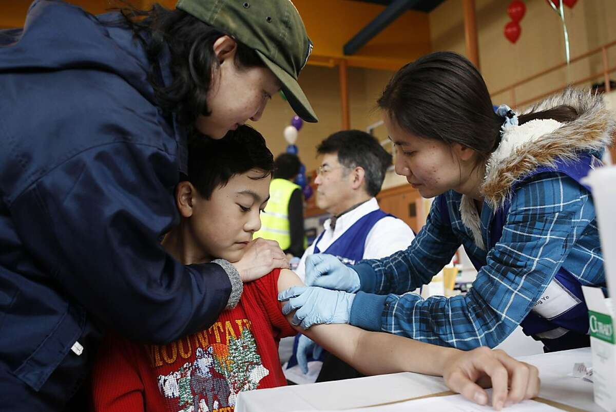 Karen Hsiung comforts her son Kameron as volunteer Wei Ye prepares his arm for a free Pertussis (whooping cough) vaccination at Roosevelt Middle School in San Francisco Calif, on Saturday, March 19, 2011.