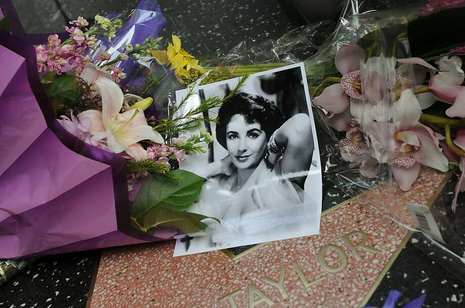 "Flowers placed by fans on Elizabeth Taylor's star at the Hollywood Walk of Fame in Hollywood, California on March 23, 2011.  Legendary Hollywood actress and violet-eyed beauty Elizabeth Taylor, who captured hearts in ""National Velvet"" to launch a film career that spanned five decades, died Wednesday aged 79. Taylor had been in Los Angeles' Cedars-Sinai hospital for six weeks with congestive heart failure, a condition with which she had struggled for some years and had recently suffered complications, a family statement said. ""She was surrounded by her children: Michael Wilding, Christopher Wilding, Liza Todd, and Maria Burton,"" it said, noting that Taylor, who married eight times, was survived by 10 grandchildren and four great-grandchildren. Photo: Mark Ralston, AFP/Getty Images"