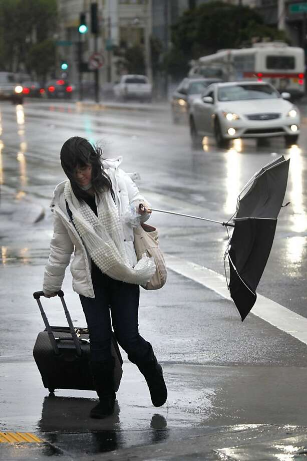 Hanqian Zhu of San Francisco battles the wind and rain as she makes her way down Van Ness Ave. with her luggage on her way to the airport on Thursday, March 23, 2011 in San Francisco, Calif. Photo: Lea Suzuki, The Chronicle