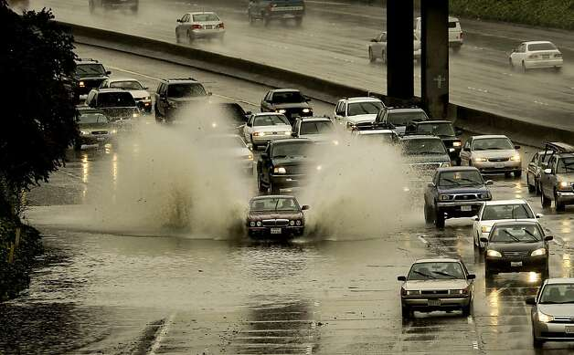 A car blasts through the rain flooded  west bound lanes of the I-580  freeway,  in Oakland, Ca., at the 38th Ave. over crossing, on Thursday Mar. 24, 2011, as heavy rainstorms rolled through Northern California. Photo: Michael Macor, The Chronicle