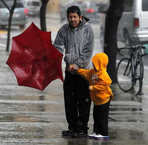 A man and child seem helpless after their umbrella collapsed in downtown San Francisco during a fierce storm Thursday March 24, 2011. Photo: Lance Iversen, The Chronicle