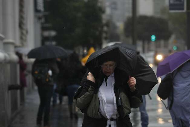 Pedestrians battle the wind and rain as they make their way down Van Ness Avenue on Thursday, March 23, 2011 in San Francisco, Calif. Photo: Lea Suzuki, The Chronicle