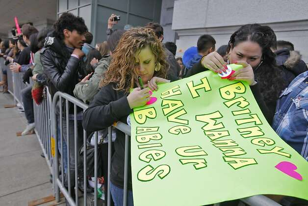 "Brittany Jewel, right and Raquel Fernandez create a sign as they wait in line outside the Bill Graham Civic Auditorium to see the popstar princess Britney Spears perform, Sunday March 27, 2011, in San Francisco, Calilf. Spears performed three songs to a free audiance for the ""Good Morning Amercian"" spring concert series and to introduce her new album Femme Fatale which goes on sale Tuesday. Photo: Lacy Atkins, The Chronicle"