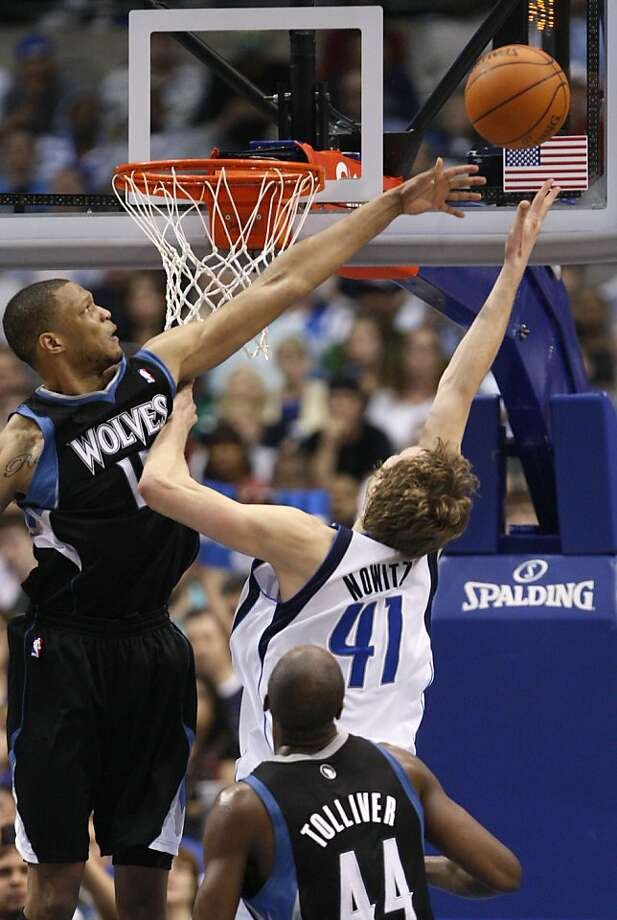 Dallas Mavericks power forward Dirk Nowitzki (41) of Germany shoots against Minnesota Timberwolves' Anthony Randolph (15) and Anthony Tolliver (44) during the second half of the NBA basketball game in Dallas, Thursday, March 24, 2011. Photo: LM Otero, AP