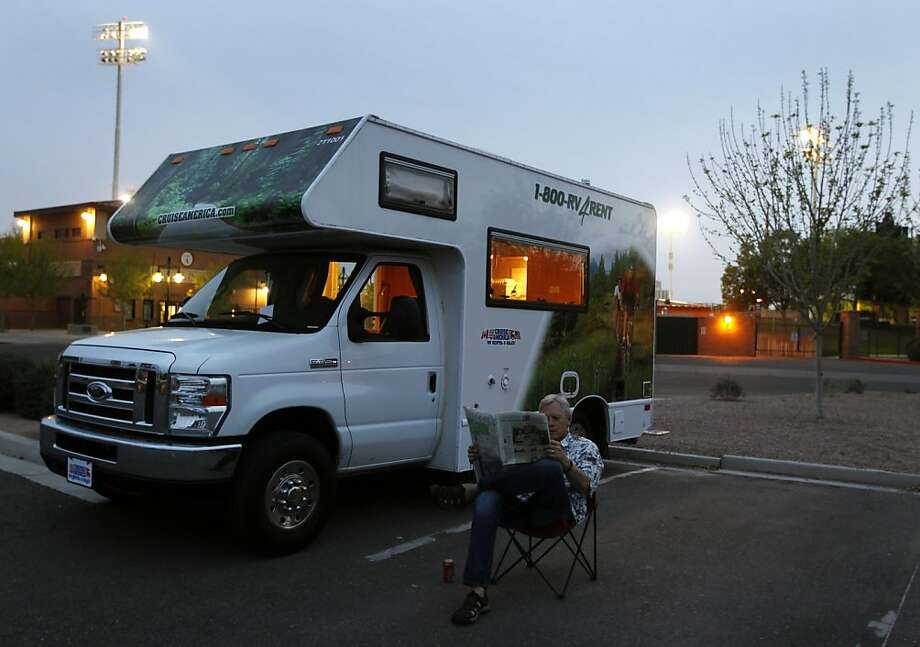 Columnist Scott Ostler settles in with a newspaper in front of his rented motor home in a parking lot behind center field at Scottsdale Stadium in Scottsdale, Ariz. on Sunday, March 20, 2011. Photo: Paul Chinn, The Chronicle