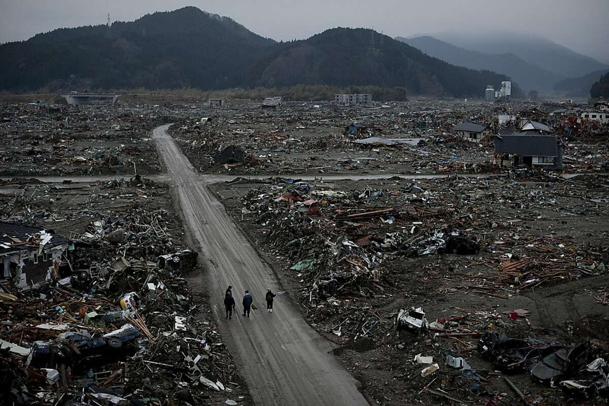 TOPSHOTS Local residents walk among destroyed houses and debris in the tsunami-damaged city of Rikuzentakata, in Iwate prefecture on March 22, 2011. The twin quake and tsunami disaster, Japan's worst crisis since World War II, has now left at least 9,079people dead and 12,645 missing, with entire communities along the northeast coast swept away.
