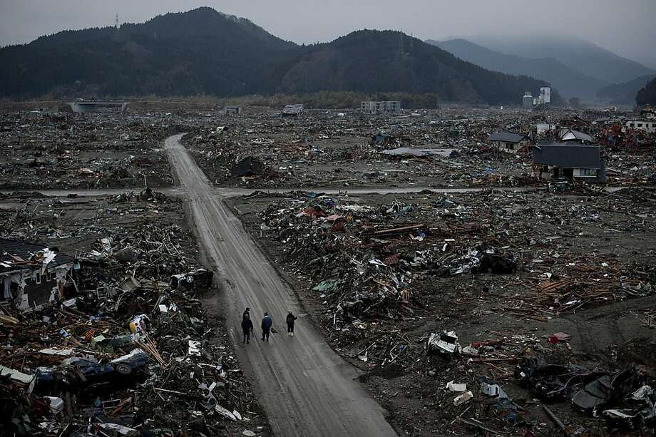 TOPSHOTS Local residents walk among destroyed houses and debris in the tsunami-damaged city of Rikuzentakata, in Iwate prefecture on March 22, 2011. The twin quake and tsunami disaster, Japan's worst crisis since World War II, has now left at least 9,079people dead and 12,645 missing, with entire communities along the northeast coast swept away. Photo: Nicolas Asfouri, AFP/Getty Images