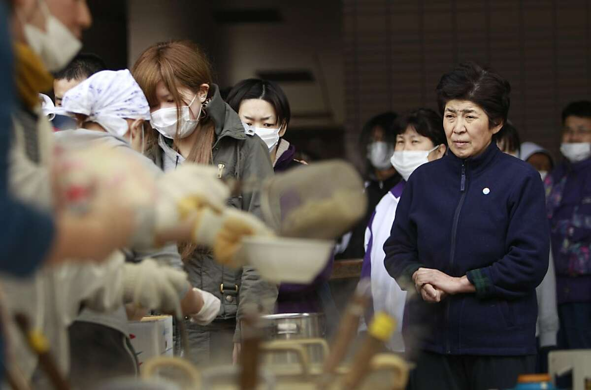 A woman waits for a bowl of soup at an evacuee center for leaked radiation from the damaged Fukushima nuclear facilities, Tuesday, March 22, 2011 in Fukushima, Fukushima Prefecture, Japan. Before the disasters, safety drills were seldom if ever practicedand information about radiation exposure rarely given in Futuba, a small town in the shadow of the nuclear plant in Fukushima Prefecture.