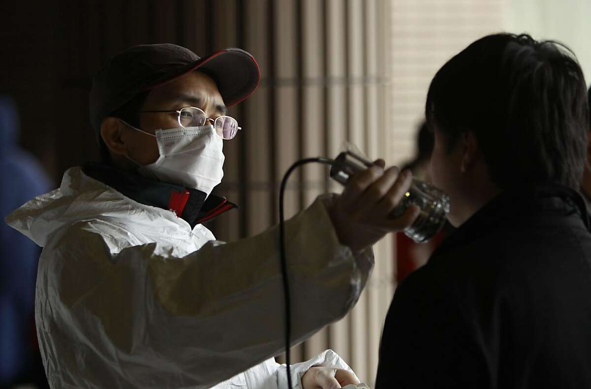A man is screened at an evacuee center for leaked radiation from the damaged Fukushima nuclear facilities, Tuesday, March 22, 2011 in Fukushima, Fukushima Prefecture, Japan. Before the disasters, safety drills were seldom if ever practiced and informationabout radiation exposure rarely given in Futuba, a small town in the shadow of the nuclear plant in Fukushima Prefecture.