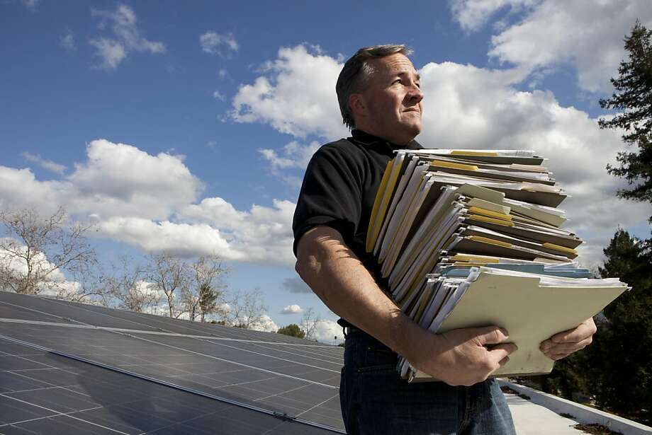Tom Sweeney, operations manager for Real Goods Solar, sits with a stack of files containing permit paperwork required by Bay Area cities for the installation of solar panels on Thursday, March 3, 2011 in Campbell, Calif.  Each permit applications costs Real Goods Solar an average of 6 man hours. Photo: John Sebastian Russo, Special To The Chronicle