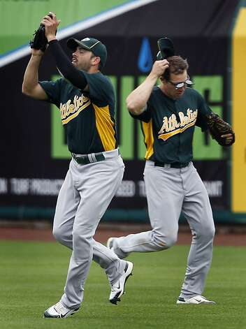David DeJesus (left) makes the play on Miguel Tejada's fly out to right field in front of Matt Carson in the fourth inning of the Oakland A's 6-4 win over the San Francisco Giants in a spring training game at Scottsdale Stadium in Scottsdale, Ariz., on Sunday. Photo: Paul Chinn, The Chronicle