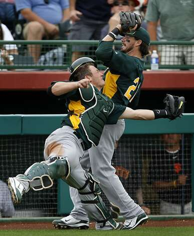 Oakland catcher Josh Donaldson and third baseman Andy LaRoche collide in foul territory and LaRoche holds onto the ball for the third out in the third inning of the Oakland A's 6-4 win over the San Francisco Giants in a spring training game at Scottsdale Stadium in Scottsdale, Ariz., on Sunday. Photo: Paul Chinn, The Chronicle